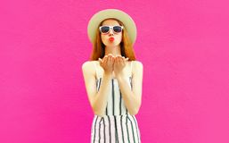 Portrait stylish pretty woman sending sweet air kiss in summer round straw hat, white striped jumpsuit on colorful pink wall royalty free stock photography