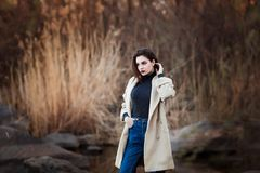 Portrait of a Stylish Pretty Young Woman in Autumn Fashion Coat walking outdoors. Royalty Free Stock Images