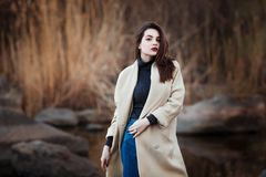 Portrait of a Stylish Pretty Young Woman in Autumn Fashion Coat walking outdoors. Stock Photos