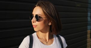 Portrait of stylish serious girl with glasses posing in city. stock image