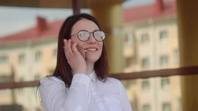 Portrait of stylish smiling business woman in fashionable clothes calling on mobile phone near office. Slow motion shot. Portrait of stylish smiling business stock video footage