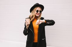Portrait stylish smiling woman with smart watch using voice command recorder or takes calling holding coffee cup on city street. Gray wall background stock image