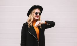 Portrait stylish smiling woman with smart watch using voice command recorder or takes calling. On city street, gray wall background royalty free stock image