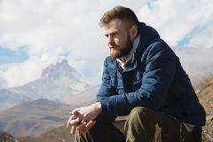 A portrait of a stylish smirk bearded hipster sitting on a rock against the backdrop of epic rocks and contemplating. Into the distance thinking about life. The Stock Photography