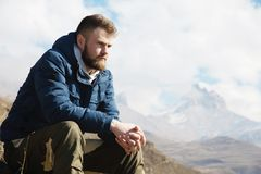 A portrait of a stylish smirk bearded hipster sitting on a rock against the backdrop of epic rocks and contemplating. Into the distance thinking about life. The royalty free stock photo