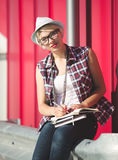 Portrait of stylish student girl writing in notebook on street Royalty Free Stock Photos