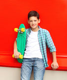 Portrait stylish teenager boy wearing a checkered shirt with skateboard in city Royalty Free Stock Images
