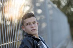 Portrait of a stylish teenager standing against a fence royalty free stock photos