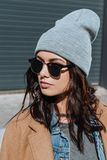 Portrait of stylish woman in autumn outfit and black sunglasses standing outside royalty free stock image