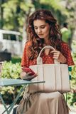 Portrait of stylish woman with bag using smartphone while sitting on terrace. In cafe royalty free stock image