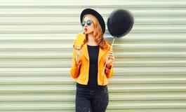 Stylish woman drinking fruit juice holding black air balloon. Portrait stylish woman drinking fruit juice holding black air balloon in round hat, yellow jacket royalty free stock photography