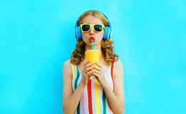 Portrait stylish woman drinking fruit juice listening to music in wireless headphones on colorful blue. Background royalty free stock photography