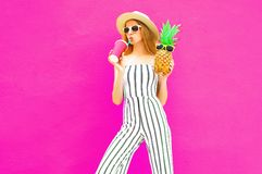 Portrait stylish woman drinking juice holding pineapple in summer round hat, white striped jumpsuit on colorful pink wall. Background royalty free stock image