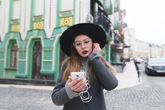 Portrait of a stylish woman listening to music in headphones on the backdrop of a beautiful old town. Beautiful woman uses a phone on the background of a Royalty Free Stock Photography