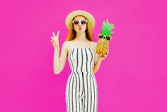 Portrait stylish woman sending sweet air kiss with pineapple in summer round straw hat, white striped jumpsuit on colorful pink royalty free stock photography