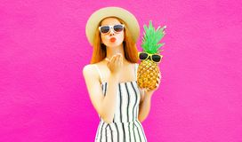 Portrait stylish woman sending sweet air kiss with pineapple in summer round straw hat, white striped jumpsuit on colorful pink stock photography
