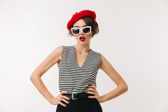 Portrait of a stylish woman wearing red beret. And sunglasses posing while standing isolated over white background Royalty Free Stock Images