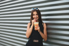 Portrait of stylish young beautiful hipster woman in little black dress drinking lemonade outdoors Royalty Free Stock Photography
