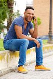 Stylish young black man sitting by the street and talking on mobile phone Royalty Free Stock Images