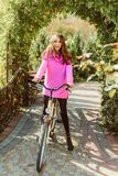 Portrait of stylish young girl standing with her bike in the park. Pretty long-hair woman ready to ride outside on her stock image