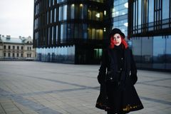 Portrait of stylish young happy woman in black coat and hat against modern building Stock Image