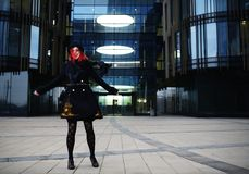 Portrait of stylish young happy woman in black coat and hat against modern building Stock Photography