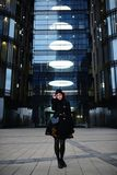 Portrait of stylish young happy woman in black coat and hat against modern building Royalty Free Stock Photos