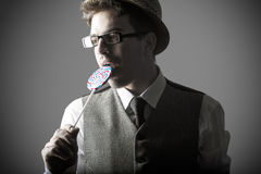 Portrait of stylish young man eating lollipops Royalty Free Stock Photo