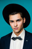 Portrait of a stylish young man in hat wearing elegant suit. Royalty Free Stock Images