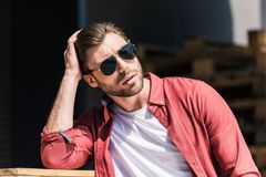 Portrait of stylish young man. In sunglasses holding hand on haircut royalty free stock image