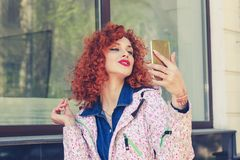 Bold girl taking selfie with her smart phone. Portrait of stylish young redhead curly woman near her apartment complex outdoors taking selfie with her smart stock photo