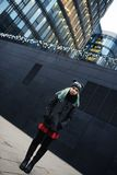 Portrait of stylish young sad woman in black coat and hat against modern building Stock Photos