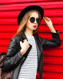 Portrait stylish young woman in black rock style stands over red Stock Photos