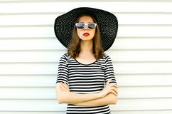 Portrait stylish young woman in black summer straw hat posing on white wall. Background stock image