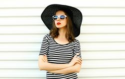 Portrait stylish young woman in black summer straw hat posing on white wall. Background stock photography