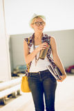 Portrait of stylish young woman walking on street at sunny day Stock Photography