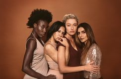 Portrait of stylish young women. Standing over brown background. Multi ethnic fashion models posing together in studio Royalty Free Stock Photos