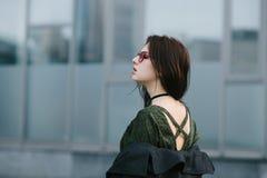 Portrait stylishly dressed brunette girl in glasses that reveals their backs on gray blurred background. Portrait stylishly dressed brunette girl in glasses that Stock Photo