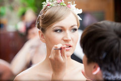 Portrait of stylist making makeup for blonde bride Stock Photography