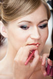 Portrait of stylist painting brides lips with lipstick Royalty Free Stock Photo