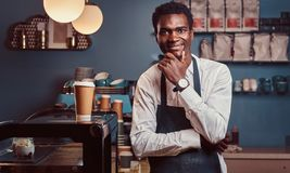 Portrait of successful African American owner small business smiling at camera while standing at the coffee shop. stock images