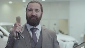 Portrait of a successful bearded business man in a business suit showing the key of a luxury car looking into the camera.  stock footage