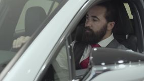Portrait successful bearded man sitting in passenger compartment of the new vehicle inspects the interior of the newly. Successful couple sitting in passenger stock video