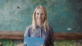 Portrait of successful beautiful blonde businesswoman at loft coworking space. Female holds the document, smiling. Stock Photo