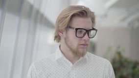 Portrait successful blond man in glasses standing in a light comfortable office looking at the camera. Handsome. Businessman involved in his work. Workplace stock video footage