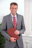 Portrait of successful business man holding folder Stock Photography