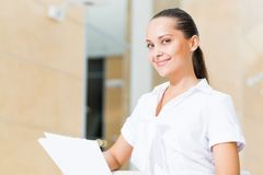 Portrait of a successful business woman. In the office, holding papers and smile Royalty Free Stock Photography