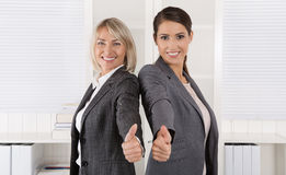 Portrait: Successful business woman team making thumbs up gestur Stock Photo