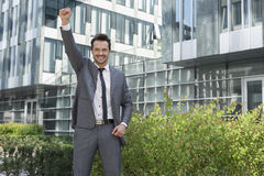 Portrait of successful businessman with arm raised standing outside office building Stock Images