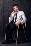 Portrait of successful businessman on a chair. On black background Stock Photography